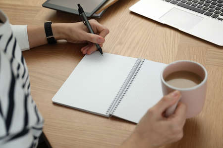 Left-handed woman with cup of coffee writing in notebook at wooden table, closeup