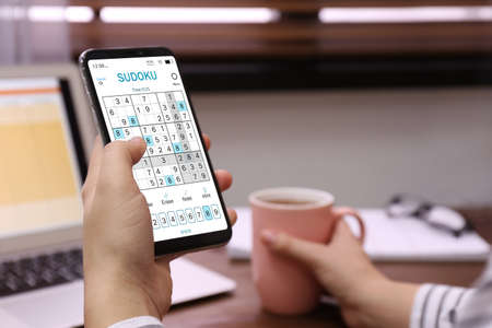 Woman playing sudoku game on smartphone indoors, closeup