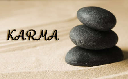 Karma concept. Stacked stones on sand, closeup