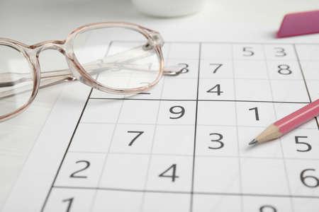 Sudoku, pencil and eyeglasses on white table, closeup