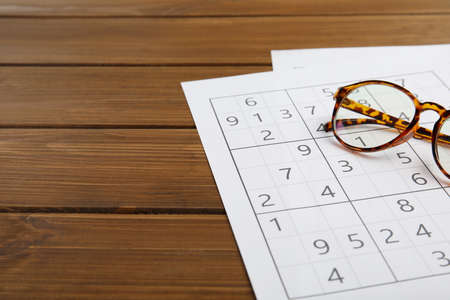 Sudoku and eyeglasses on wooden table, space for text