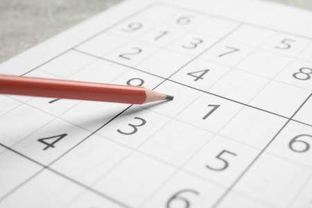 Sudoku and pencil on grey table, closeup