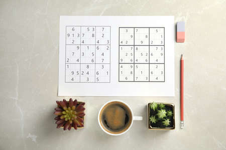Sudoku, pencil, eraser, cup of coffee and houseplants on light grey table, flat lay