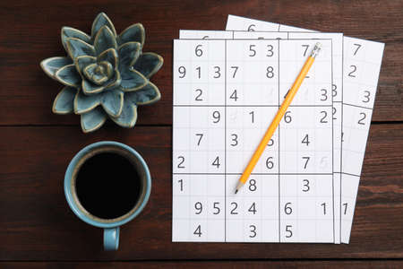 Sudoku, pencil, cup of coffee and decorative succulent on wooden table, flat lay
