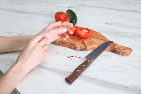 Young woman cutting finger with knife while cooking at white marble table, closeup