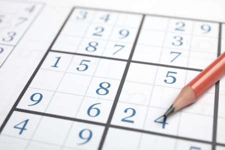 Sudoku puzzle grid and pencil, closeup view