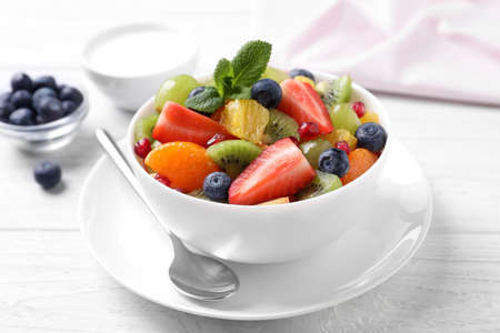 Delicious fresh fruit salad in bowl on white wooden table Archivio Fotografico