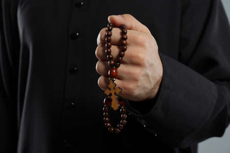 Priest in cassock with rosary beads, closeup