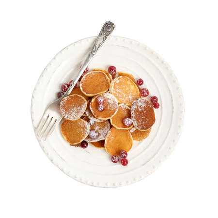 Delicious mini pancakes cereal with cranberries on white background, top view