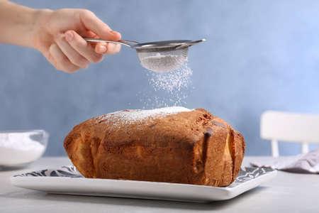 Woman sifting sugar powder onto fresh cake on light table, closeup Standard-Bild