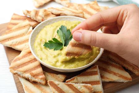 Woman dipping pita chip into hummus at table, closeup Stockfoto