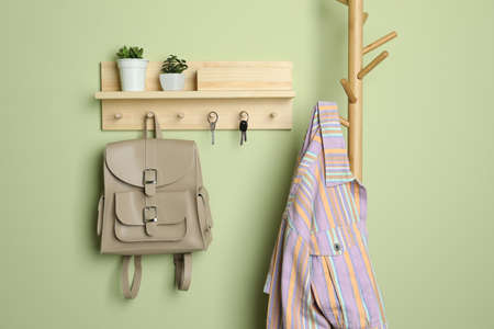 Wooden hanger for keys on light green wall