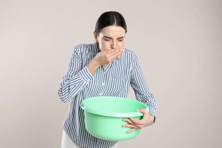 Woman with basin suffering from nausea on beige background. Food poisoning