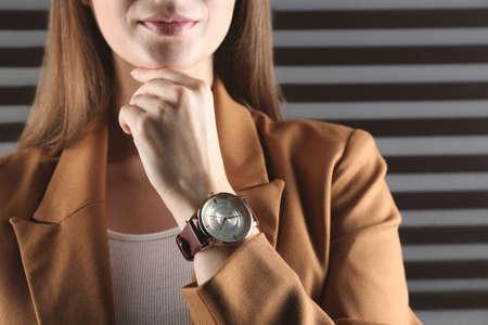 Woman wearing luxury wristwatch on dark grey background, closeup Stock Photo