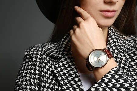 Woman wearing luxury wristwatch on grey background, closeup Stock Photo