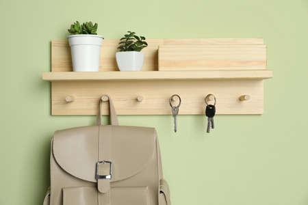 Wooden hanger for keys on light green wall Foto de archivo