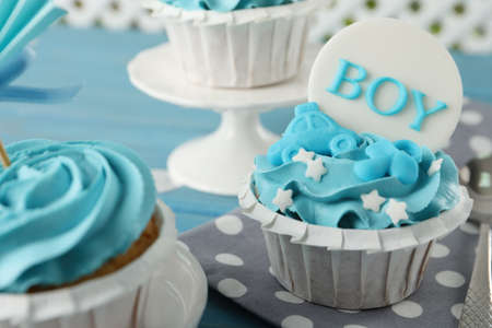 Delicious cupcakes with light blue cream and toppers for baby shower on table, closeup Stockfoto
