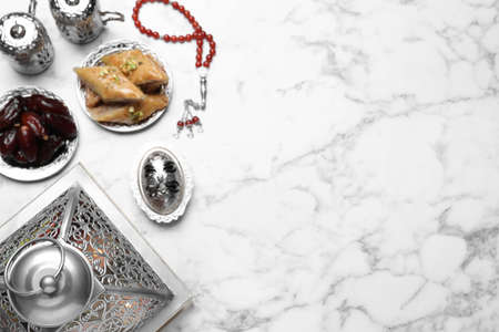 Flat lay composition with Arabic lantern and snacks on white marble table . Space for text