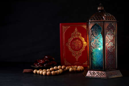与阿拉伯灯笼和古兰经的构成在黑桌上。文本的空间