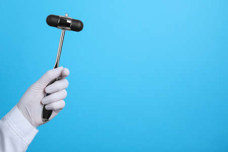 Doctor holding reflex hammer on light blue background, closeup with space for text. Nervous system diagnostic