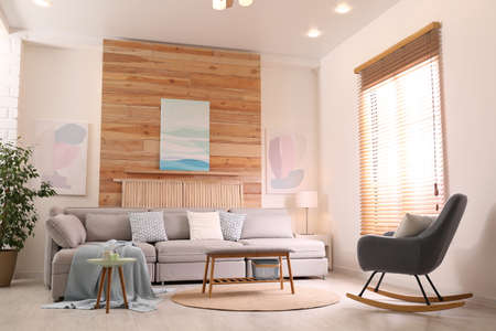 Stylish living room interior with comfortable sofa and pictures