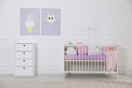 Crib and dresser near wall with pictures in cozy baby room. Interior design