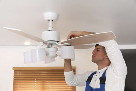 Electrician repairing ceiling fan with lamps indoors