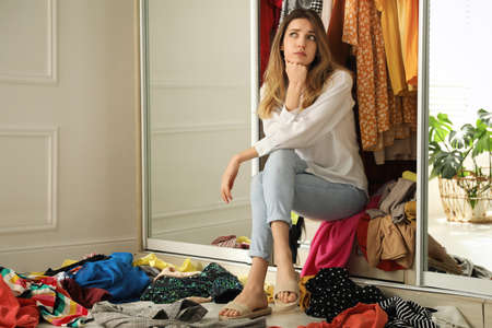 Young woman sitting in wardrobe with different clothes indoors. Fast fashion concept