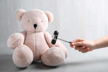 Woman pretending to test teddy bear's reflexes with hammer on grey background, closeup. Nervous system diagnostic Stock Photo