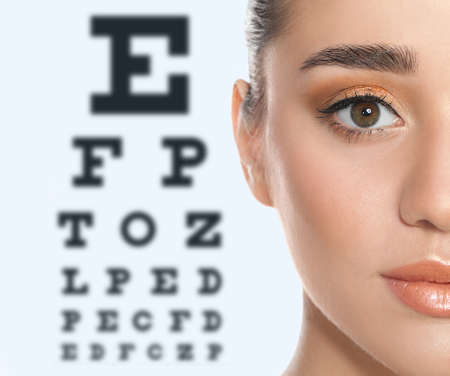 Young woman and blurred eye chart on background. Visiting ophthalmologist