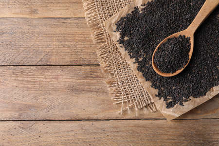 Black sesame seeds and spoon on wooden table, flat lay. Space for text