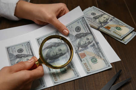 Counterfeiter examining sheet of paper with dollar banknotes at wooden table, closeup. Fake money concept