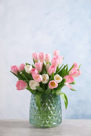 Beautiful bouquet of tulips in glass vase on light table