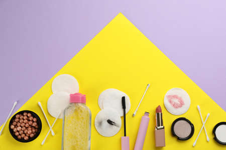 Dirty cotton pads, swabs, cosmetic products and micellar cleansing water on color background, flat lay Imagens