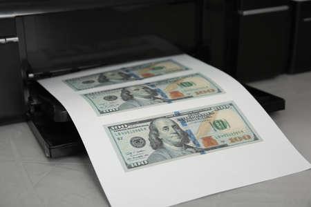 Printing dollar banknotes on grey table, closeup. Fake money concept