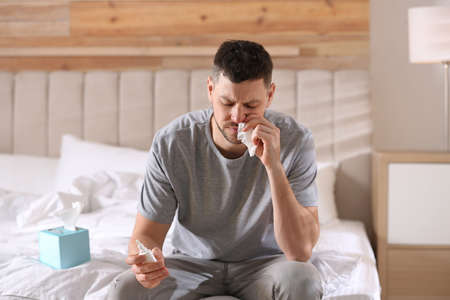 Ill man with nasal spray and paper tissue on bed at home