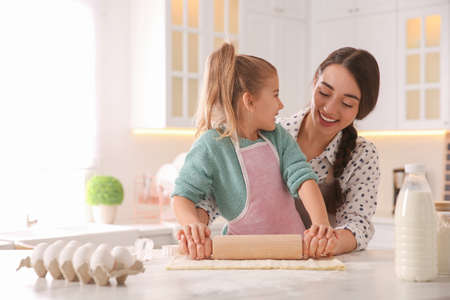 Mother and daughter rolling out dough in kitchen at home