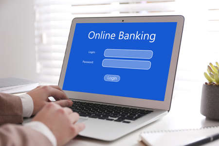Woman using online banking application on laptop at table, closeup Фото со стока