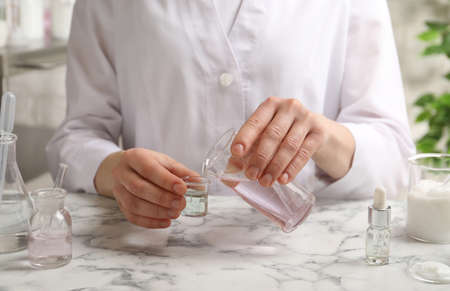 Scientist testing cosmetic product at white marble table in laboratory, closeup