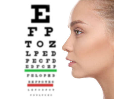 Young woman and blurred eye chart on background. Visiting ophthalmologist Stock Photo