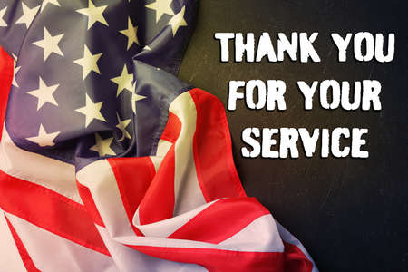 Text THANK YOU FOR YOUR SERVICE and American flag on black background, top view. Memorial day