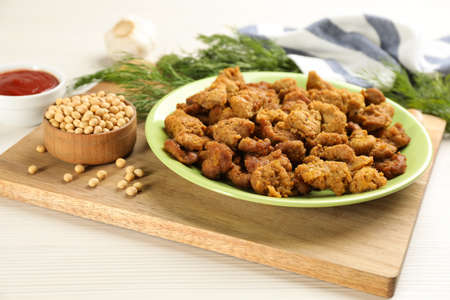 Cooked soy meat in bowl on white wooden table
