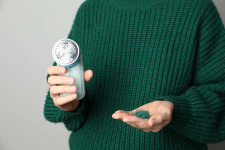 Woman in woolen sweater holding fabric shaver and lint on light grey background, closeup