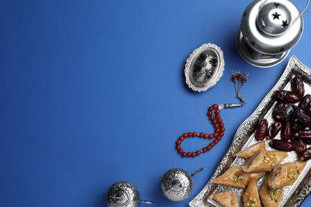 Flat lay composition with Arabic lantern and snacks on blue background. Space for text