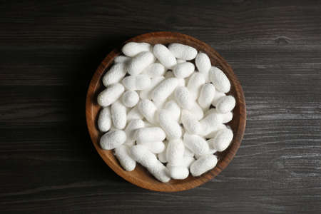 White silk cocoons in bowl on wooden table, top view