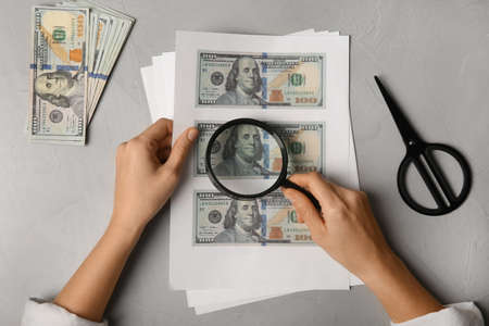 Counterfeiter examining sheet of paper with dollar banknotes at grey table, top view. Fake money concept