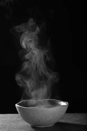 Bowl with steam on table against black background Foto de archivo