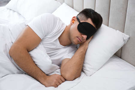 Man with foam ear plugs and mask sleeping in bed