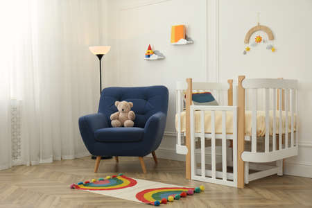 Cute baby room interior with stylish furniture and toys