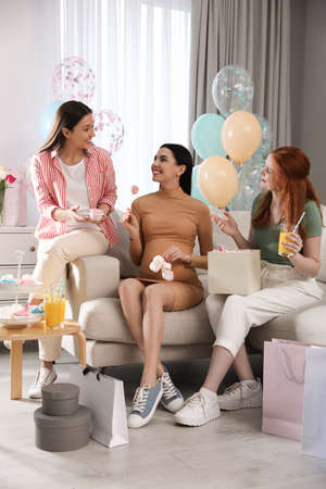 Happy pregnant woman spending time with friends at baby shower party